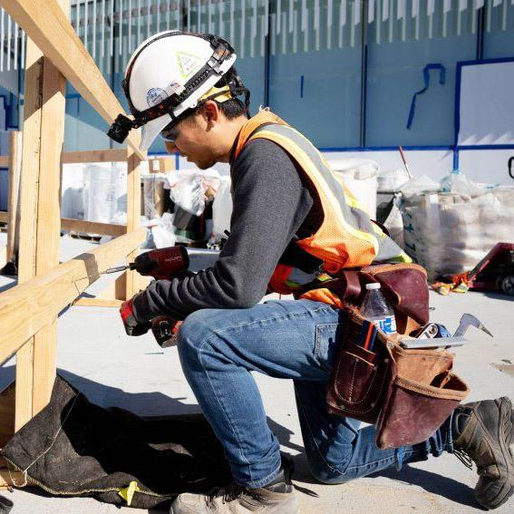 A construction worker kneels as he drills into a wood board