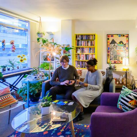 Two UCSFers sit in their colorful living room