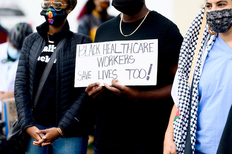 A Blackcare health worker holds a sign saying Black healthcare workers save lives too