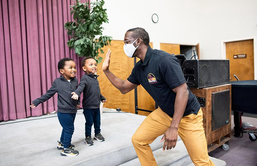 onathan Butler high fives two young twins at a vaccination event in a Black church