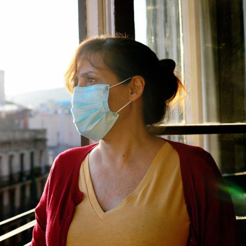 A woman wearing a mask gazes out of a window