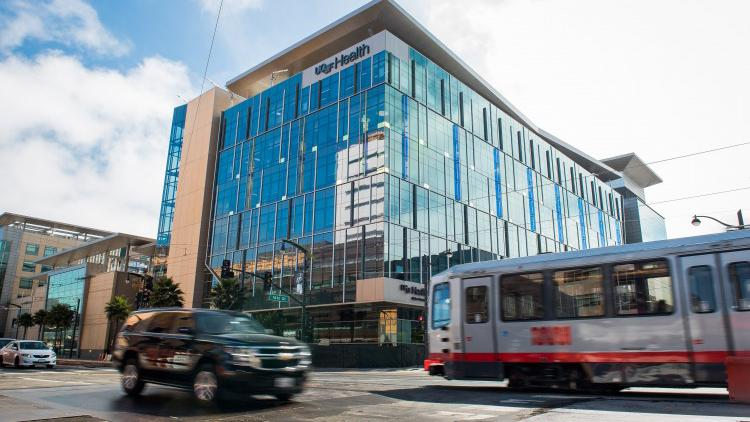 Bus and car driving past UCSF Health building
