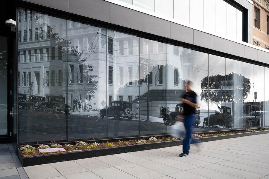 A blurred person walks past the new entrance of the Clinical Sciences Building where you can see a historical photo beyond the glass windows