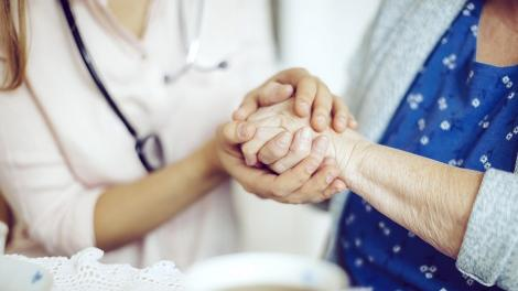 Doctor holding a older woman's hand