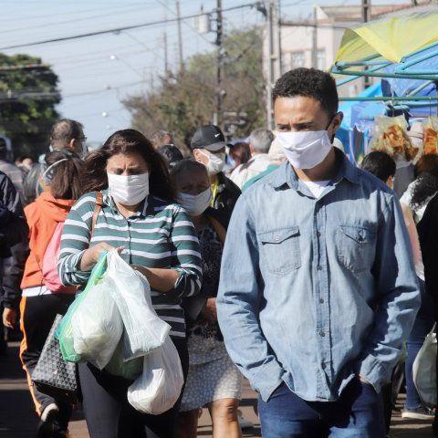 Masked shoppers walk down a street in Brazil