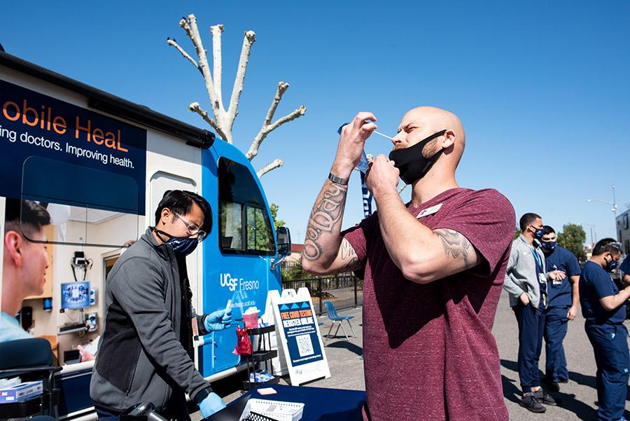 A man swabs his nose in front of a mobile vaccination truck run by UCSF Fresno