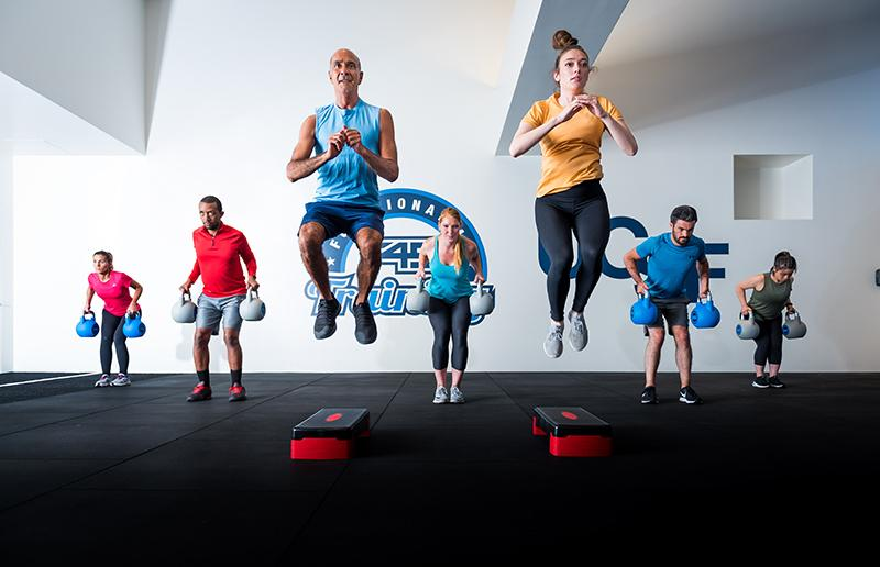 Fitness class jumping with kettle balls