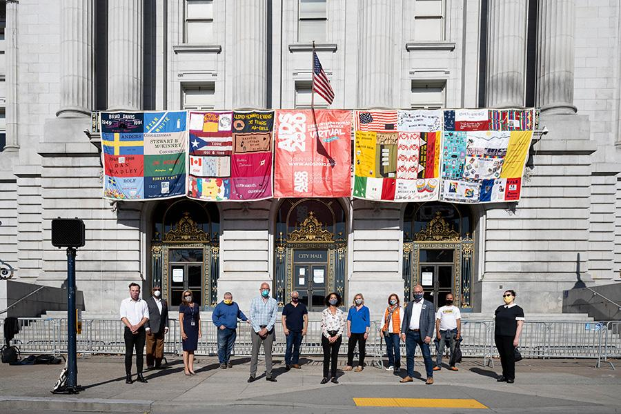 UCSFers standing outside City Hall with the AIDS quilt hanging overhead