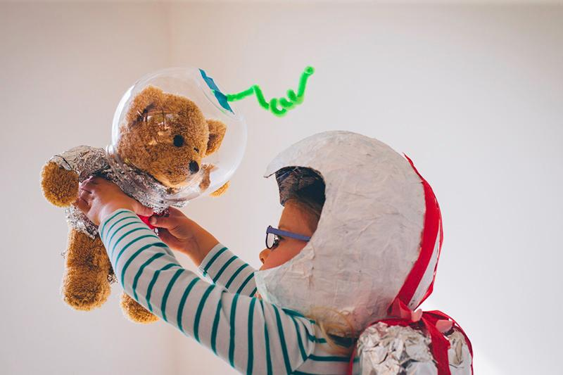 Child wearing a homemade helmet with a teddy bear