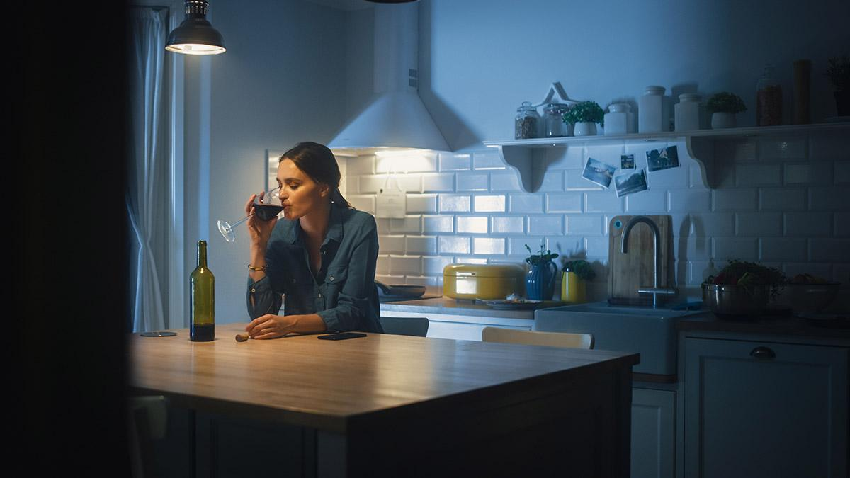 Woman drinking a glass of wine alone in her kitchen