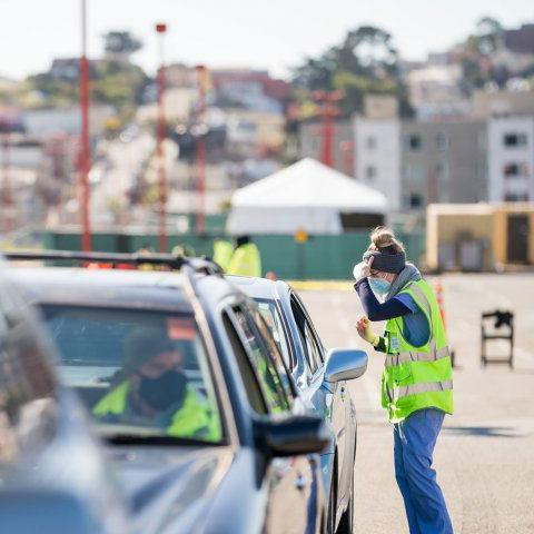Person wearing a yellow vest speaking with a driver at a drive through vaccination site