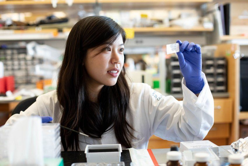Victoria Chang wears a lab coat and gloves