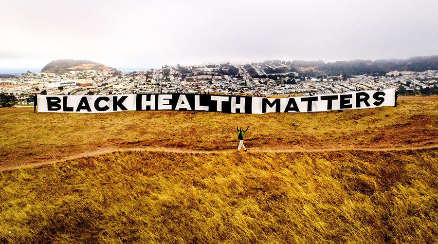 Giant Black Health Matters sign standing over a hill