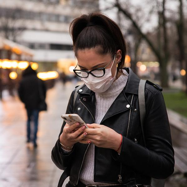 Woman checking a phone while wearing a mask outside