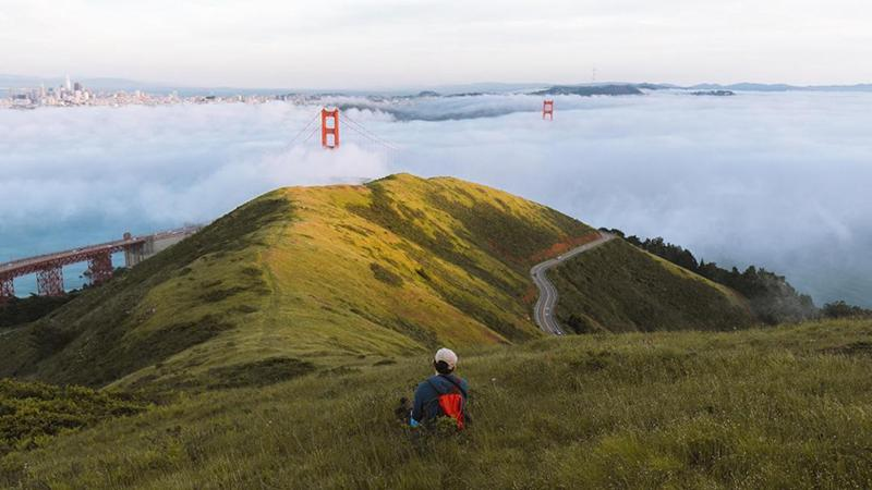 Person sitting on a grassy hill looking at the Golden Gate Bridge