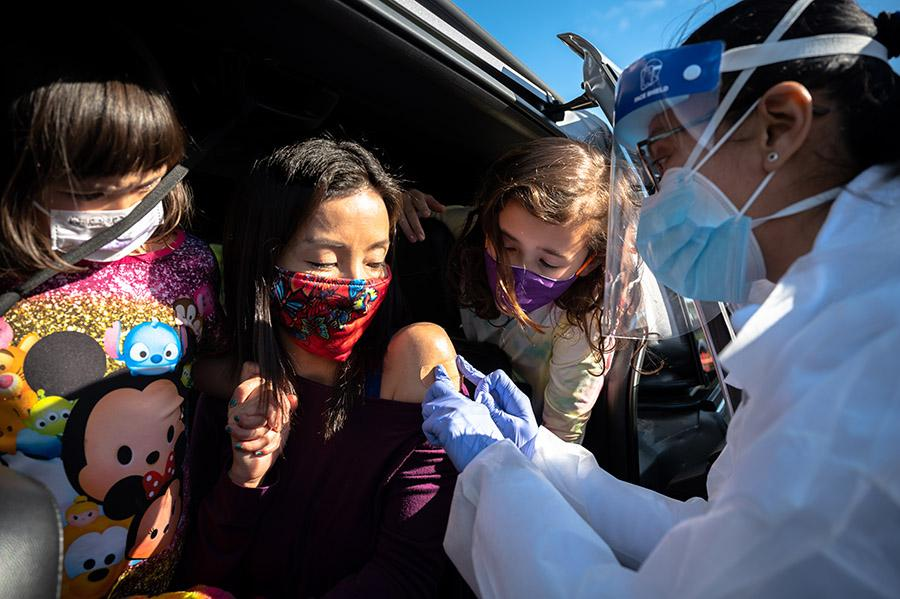 A woman receiving a vaccine from her car while her two children peer around to watch