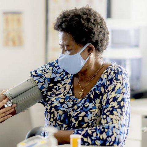Black patient getting her blood pressure taken