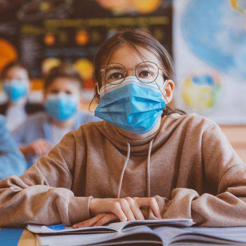 A little girl in a classroom wearing a mask