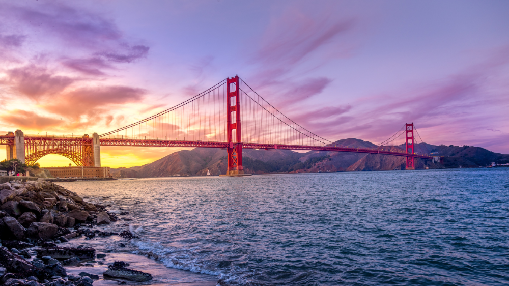 Towers of the Golden Gate Bridge over the water during a colorful sunset
