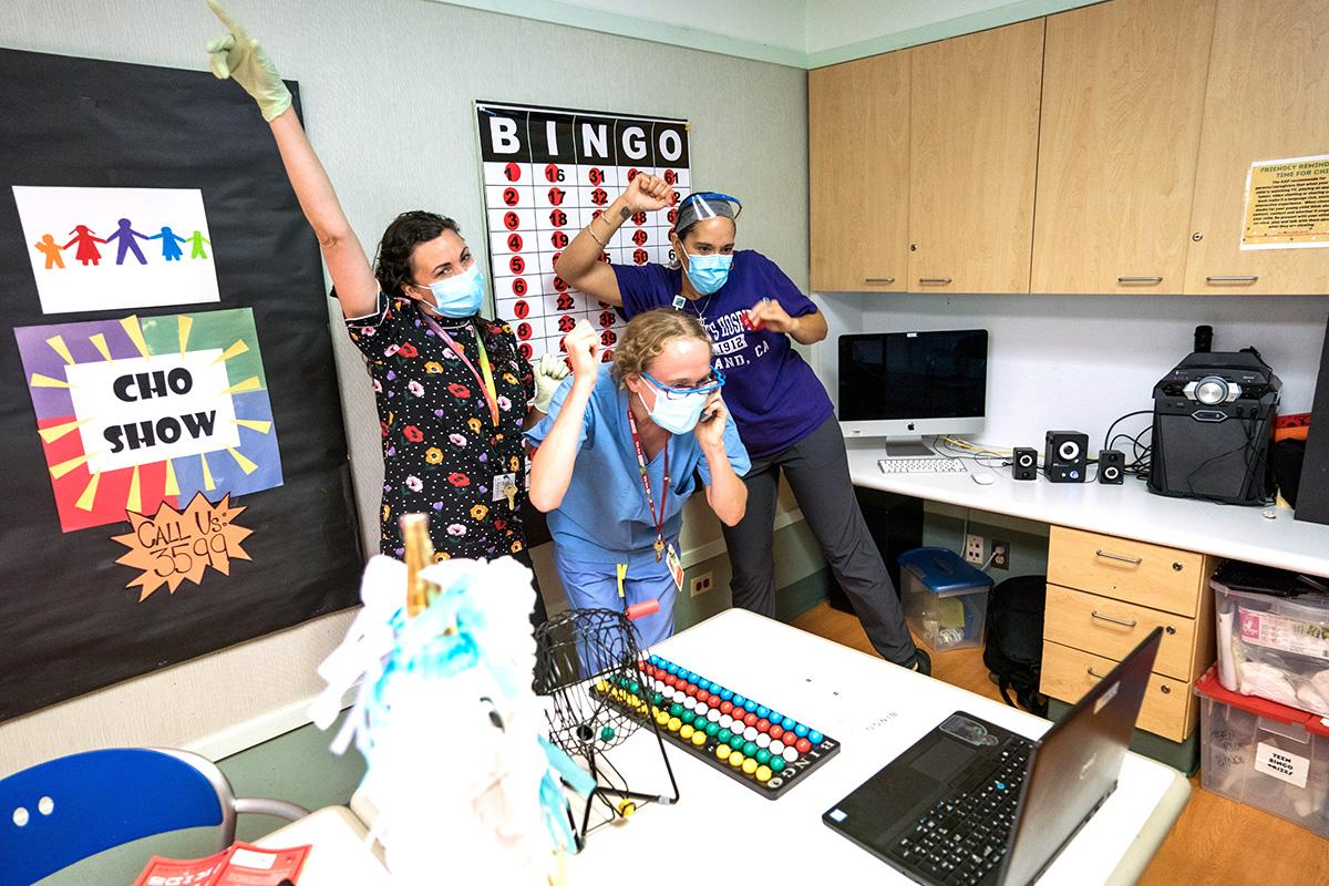 Three staff members cheer for a winner during an online bingo game at the childrens hospital