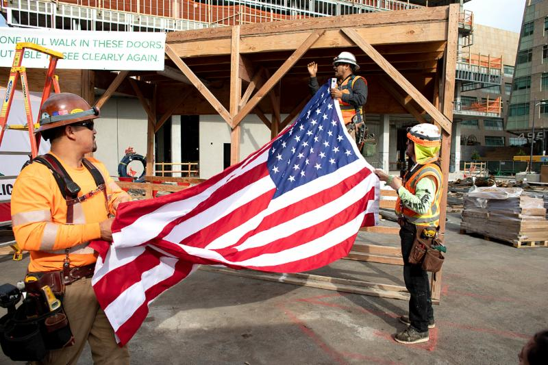Construction workers with the American flag at the topping out ceremony for Block 33
