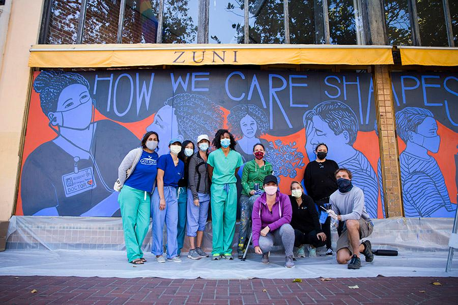 Docs standing in front of a newly painted mural  of doctors and patients