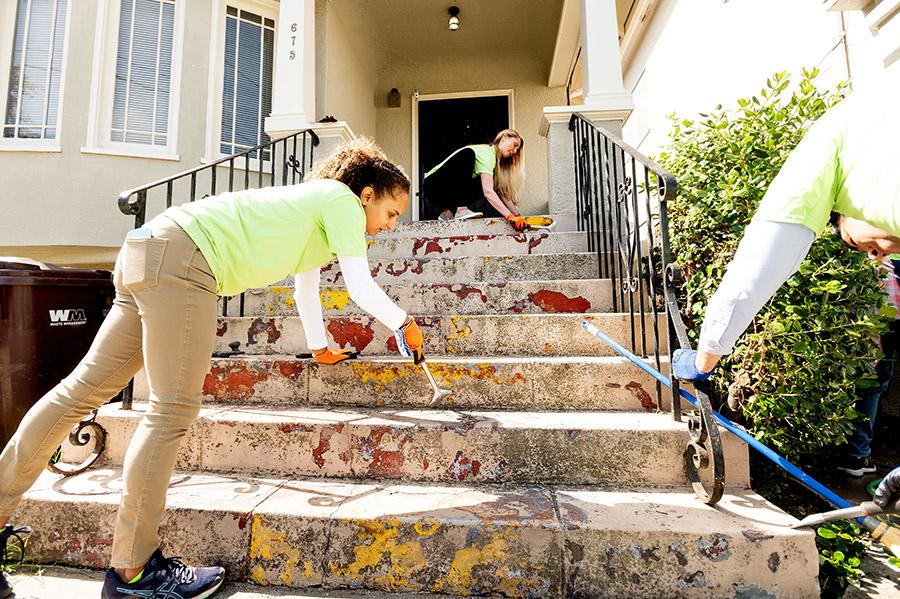 Three volunteers scrub away graffiti and paint from the stoop of a house in Oakland