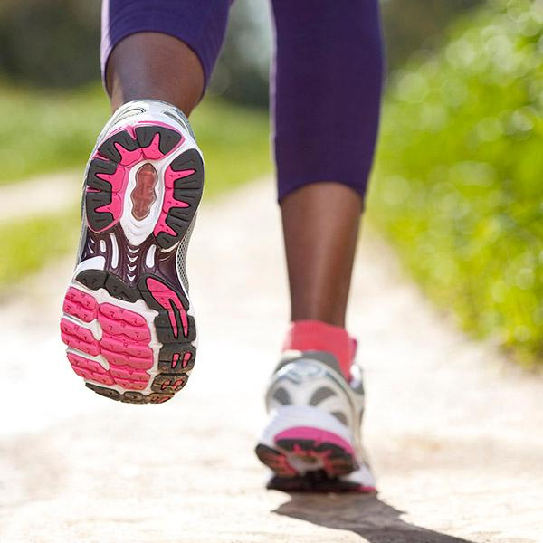 Close up of woman running in tennis shoes down a sunny path