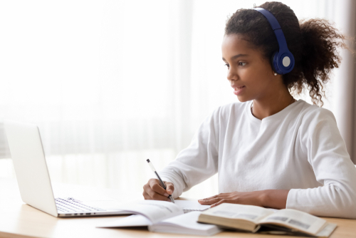 African American teen girl wearing headphones learning language online_ using laptop_ looking at screen_ doing school tasks at home_ writing notes_ listening to lecture or music_ distance education