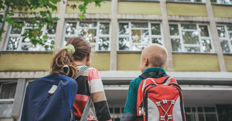 Girl and boy with backpacks looking up at a school building
