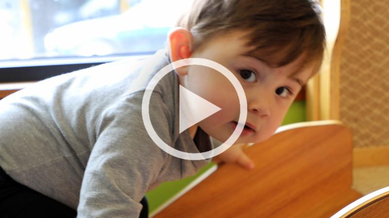 video thumbnail of a boy climbing on a slide in a nursery