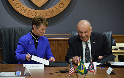 Kent State President Beverly Warren and Pontifical Catholic University of Parana President Waldemiro Gremski share a laugh during the May 3 signing ceremony formalizing the American Academy partnership.