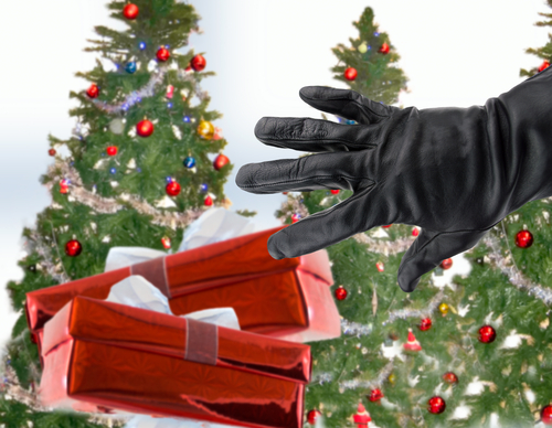 gloved black hand of a thief stealing Christmas gifts next the xmas trees