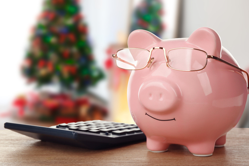 Holiday expenses concept. Piggy bank with glasses on wooden table