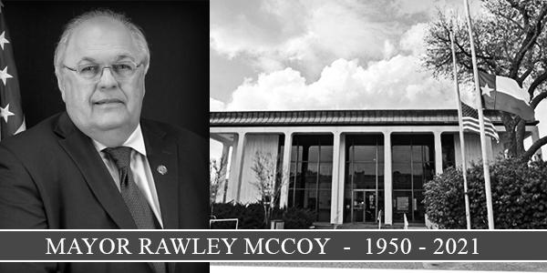 Black and white image of mayor next to City Hall with flags at half-staff. Text reads Mayor Rawley McCoy 1950 to 2021.