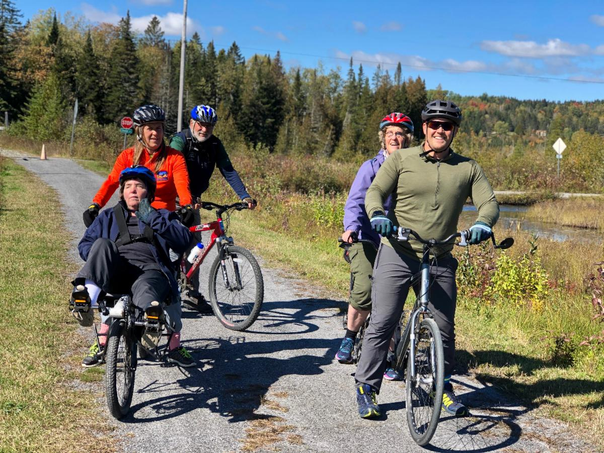 Group photo biking the Lamoille Valley Rail Trail. 6.8 miles in...half way. Cindy and Thomas are on the right on a tandem bike and Marie and Gail are on the left side of the trail. John in the back. Beautiful fall scenery and blue sky in the background.