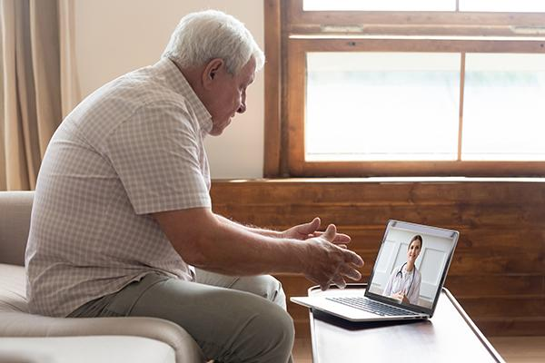 Older gentleman sits on sofa looking at laptop showing health care provider