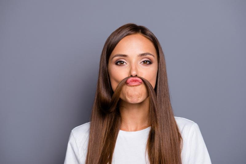 Portrait of brown-haired gorgeous nice young lady grimacing with curl_ fake mustache over grey background_ isolated
