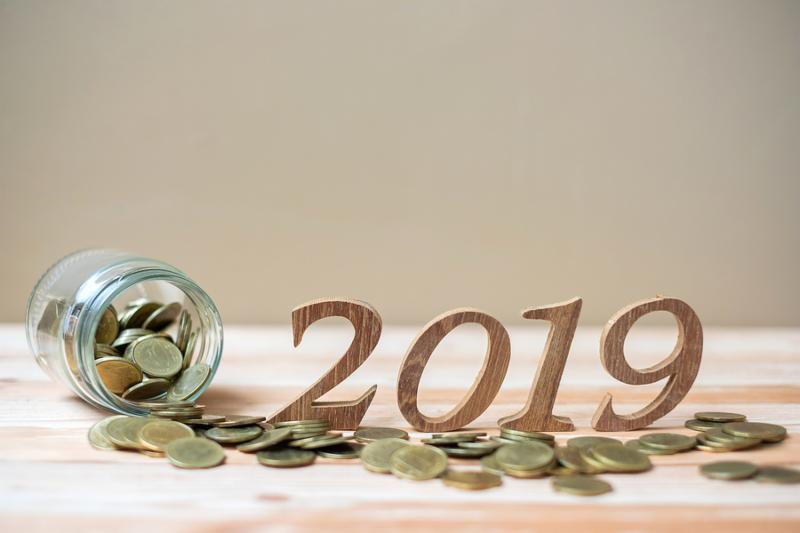2019 Happy New Year with gold coins stack and wooden number on table. business_ investment_ retirement planning_ finance_ Saving and New Year Resolution concepts
