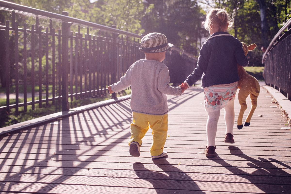 Child holding adult hand walking in sun