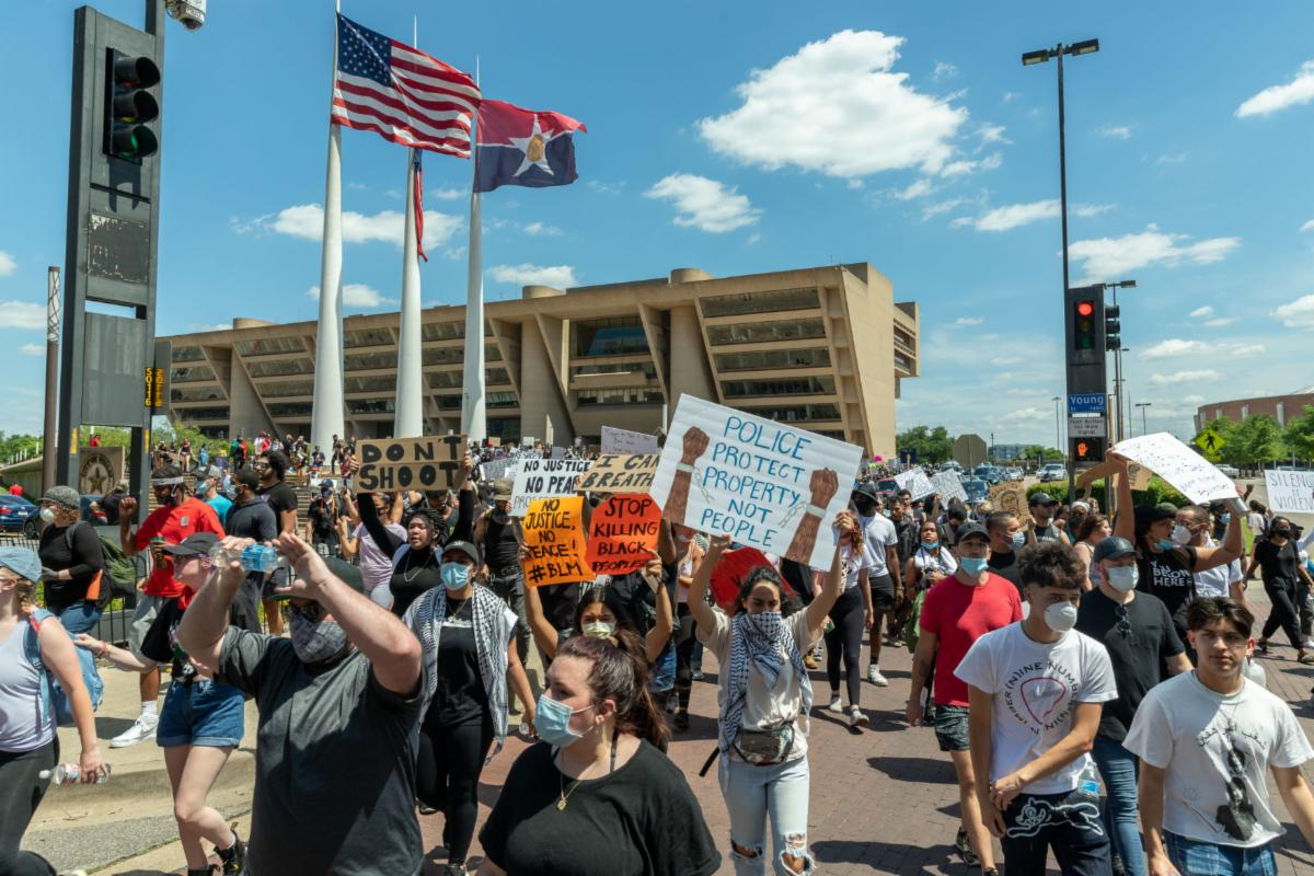 Protesters walk from City Hall during a demonstration against police brutality May 30 in Dallas. The event began with speakers in front of City Hall before moving through the streets of downtown Dallas.