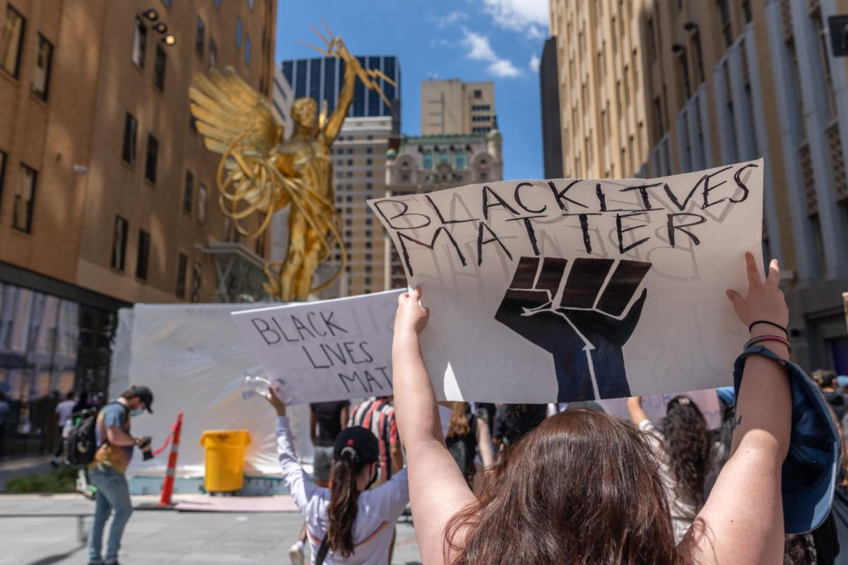 A protester raises a Black Lives Matter sign during a demonstration against police brutality May 30 in Dallas. The Office of Multicultural Affairs hosted a virtual town hall to discuss recent protests for racial equality and police brutality.