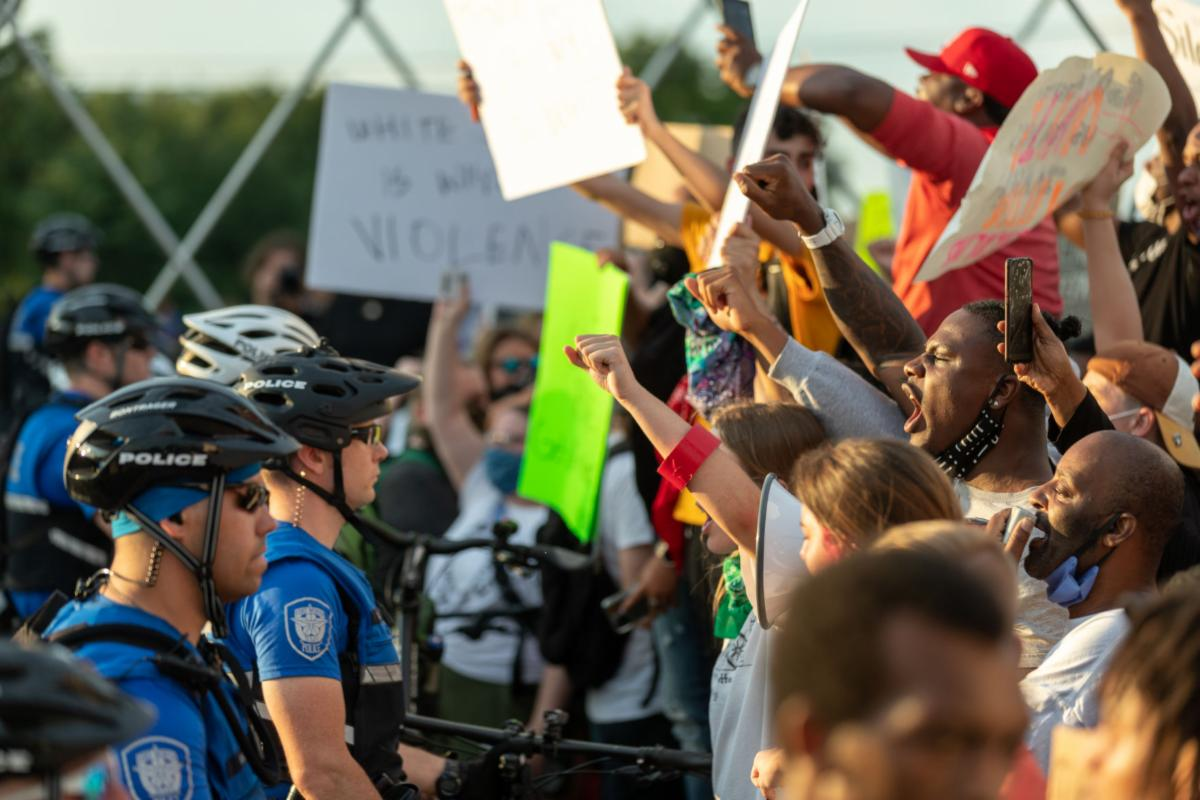 Demonstrators raise fists and yell at police May 31 in Fort Worth. Protesters were met by a line of police officers blocking the West Seventh Street bridge.