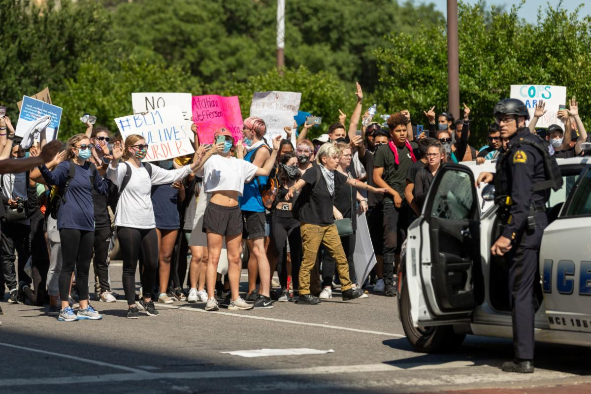 Protesters raise their hands during a demonstration against police brutality May 30 in Dallas. Dallas police announced a 7 p.m. curfew after days of protests.