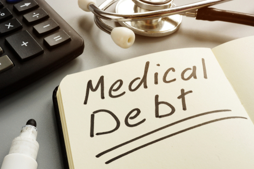 Medical debt bill and and stethoscope.