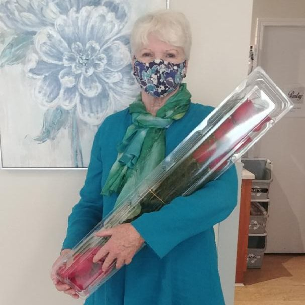 Pictured is a Transition House counsellor happily accepting delivery of 12 roses.