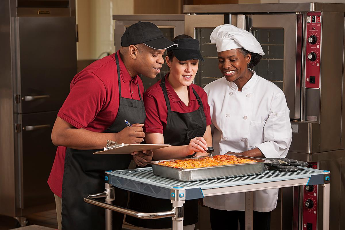 Chef and food service workers check the temperature of a dish