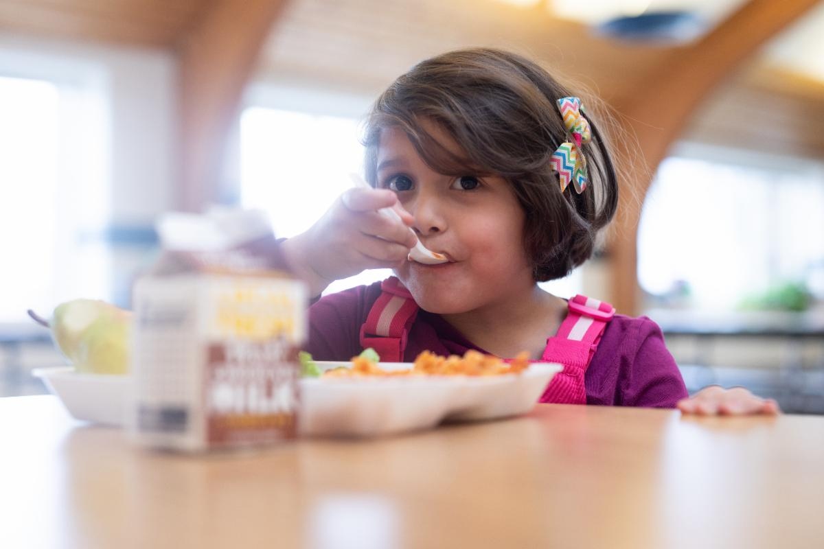 Young girl eats food off a tray at a school cafeteria table