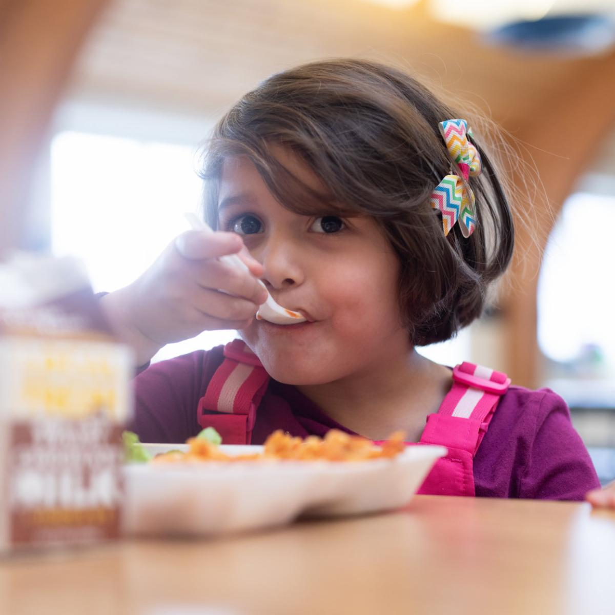 Young girl eats lunch in a school cafeteria