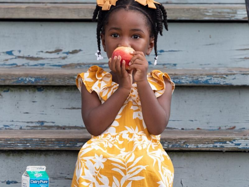 Young child eats an apple.